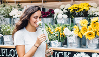 Young woman smelling a daisy before using her MIDFLORIDA VISA Signature credit card at a flower stand in Lakeland Florida.