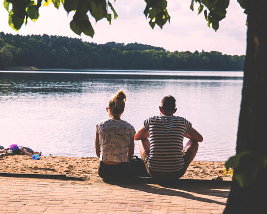 couple-sitting-by-lake