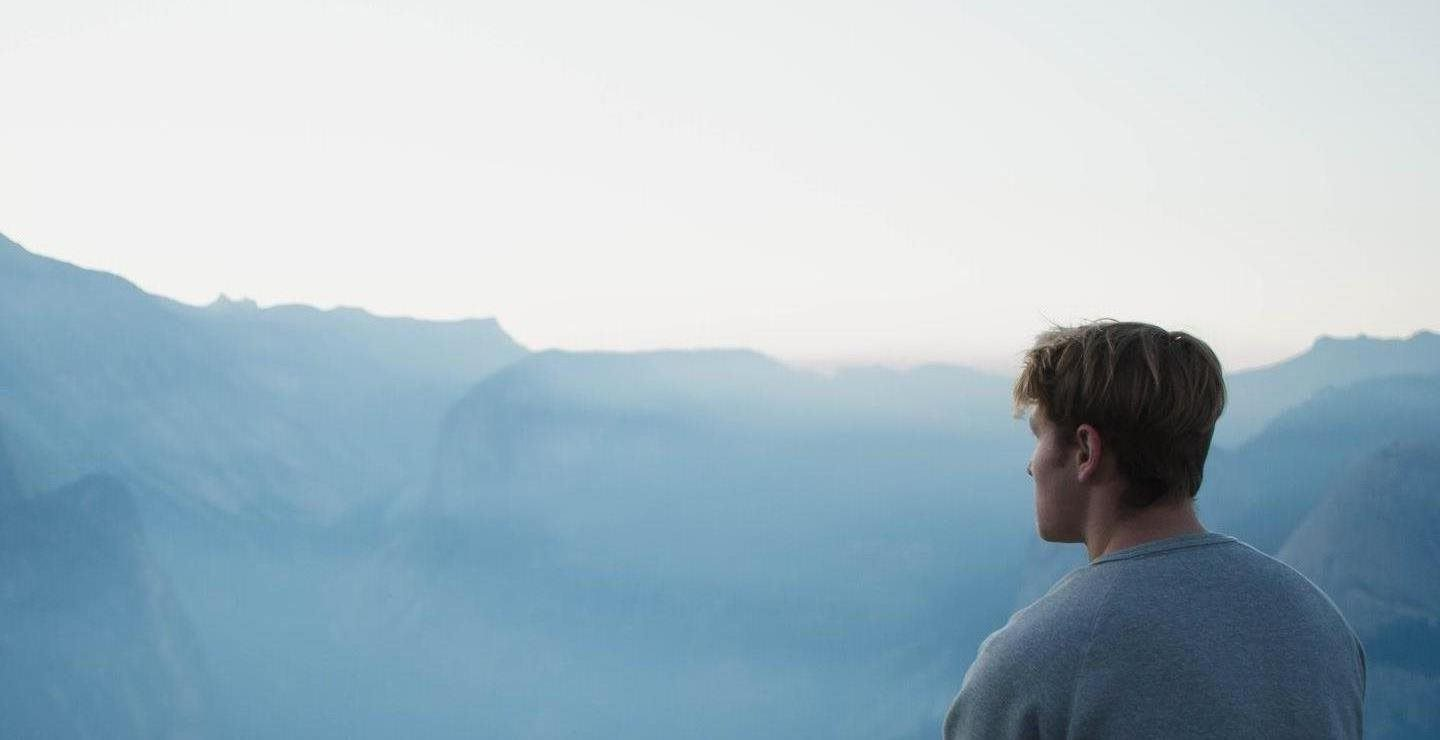Man standing in front of a mountain landscape as he thinks about financial goals.
